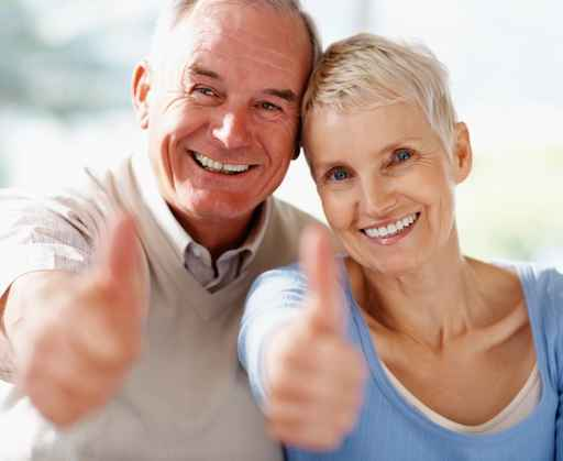 Smiling senior couple showing a success sign